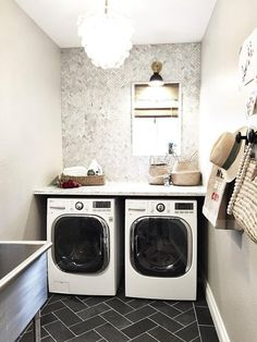 Gray laundry room features walls painted gray, Sherwin Williams Worldly Gray, lined with art and a row of hooks.