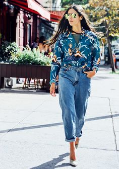 A printed cropped jacket is paired with high-waisted jeans, neutral pumps, and mirrored sunglasses