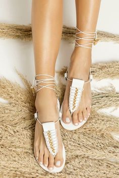 Clio lace up sandals are expertly handmade of white leather in Athens, Greece. These bohemian flats have a flattering T-strap decorated with macrame and slim ankle tie straps that are elegantly embellished with gold plated beads, coins and shells. They are great for elevating casual outfits or grounding your formal summer outfits. They also come in natural tan with both gold & silver plated embellishments and black with gold plated embellishments. Find your perfect pair of Greek sandals!