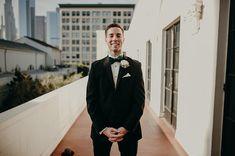 Groom style - white boutonnière - green bowtie - black tux - wedding day - city backdrop