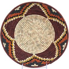Africa   Rwenzori Bowl basket woven by the women in Southern Uganda.   Baskets are woven from discarded Millet stalks, naturally dyed raffia and sometimes local grasses. The natural portions are dried millet leaves. The vibrant natural dyes used on the raffia for these tightly woven baskets come from flowers, roots, leaves and lichens grown by the weavers themselves.