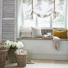 Pretty window seat area - love the neutral colored baskets and the distressed shutter