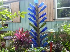 My Bottle Tree made with a 4x4 pole and spikes at a 45 angle, blue vase on top. Xmas lights in bottles.