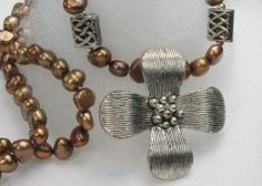 AYNX1920:             Superb 5/6mm Natural Brown Fresh Water Pearl With Tibet Silver 35mm Petal Necklace – Length 18.1inches.  This necklace is handmade each Natural Brown Freshwater pearls are unique.                 Symbolism:              Freshwater Pearls have the powers of love, money, protection, and luck.       $79.99