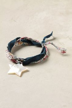 """Sky-Plucked Bracelet  style # 23659402  A pearlescent star hangs from a vintage-inspired silk strand. Both crafty and whimsical, it's perfect for gifting to your most outstanding gal. By Vanities.   Tie closure   Cotton, silk, shell   7""""L, 1""""W   France   $58"""