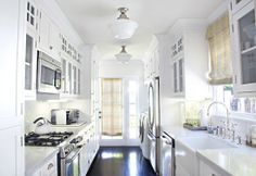 kitchens - galley white front-load washer dryer white glass-front kitchen cabinets marble countertops subway tiles backsplash farmhouse sink yellow gray custom roman shades glossy hardwood floors schoolhouse pendants