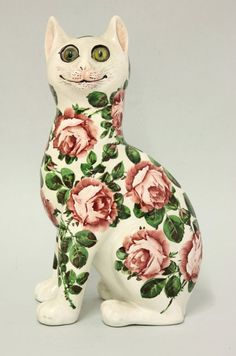 A Wemyss 'Cabbage Roses' cat, with glass eyes, impressed 'Wemyss Ware R.H.T.S', 33cm high