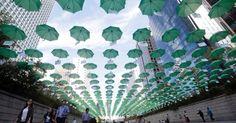 20150929 - Visitantes caminham sob guarda-chuvas que compõem exposição artística montada sobre o córrego Cheonggye, em Seul, capital da Coreia do Sul. O trabalho faz parte de uma campanha para arrecadar doações para ajudar crianças carentes do país. PICTURE: Ahn Young-joon/AP