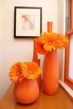 Bold, bright, monochromatic arrangements look fantastic to brighten up spaces and events! These orange Gerbera Daisies look inviting inside different sized orange vases. Shop Gerbera Daisies year-round at GrowersBox.com!