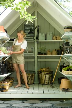 potting shed- wow. love the wire baskets holding firewood, the lamp, the silver tins, the organization box for little items on the top shelf- and even those square stepping stones in front!