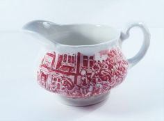 Royal Tudor Coaching Tavern's Creamer  -Marked Staffordshire England 1828 on the bottom (see picture 8)  -Color is Pink  -Scene is men, horses and a wagon on one side,  Street view of a building with a woman in the door way on the other.  -No chips or Cracks  - Holds 4 Ounces