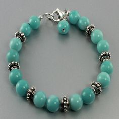 This striking bracelet is made with bluish green Amazonite gemstones and large…