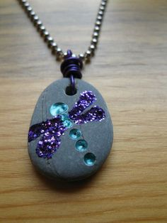 Use a dremel to make holes holes into flat stone & glitter glue &/or gems to fill them.