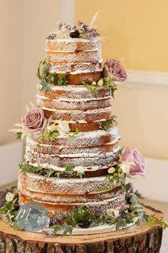 Naked cake rustique, avec quelques fleurs posé sur un socle de bois