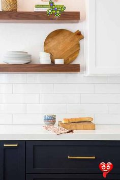 White and blue kitchen features navy blue shaker cabinets adorned aged brass pulls paired with white quartz countertops that resemble marble and a white stacked tile backsplash lined with stacked stained floating shelves.<br>
