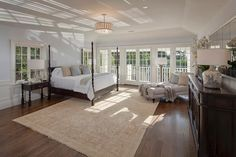 With access to a stunning balcony, this light and airy master bedroom is a welcome retreat. The classic four-poster bed and chaise lounge are placed to enjoy views of the landscape beyond. This exceptional Georgian estate in Bel-Air, Calif., was built in 1929 by architect Paul Williams and recently underwent a complete restoration.