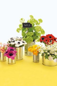 Remove the labels from tin cans of different sizes and fill with a mix of flowers. So simple but pretty and  inexpensive ..bridesmagazine.co.uk