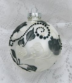 White glass ornament with Black and White 3D texture painted MUD floral design and added rhinestone bling. Each ornament I create is a one-of-a-kind. The texture medium and paint brush I use to paint the ornamnents were both created to my specifications. My signature M is located on the bottom of the ornament. Gift boxed. Measures 3 x 3 Ornament weight is 2 ounces. #77