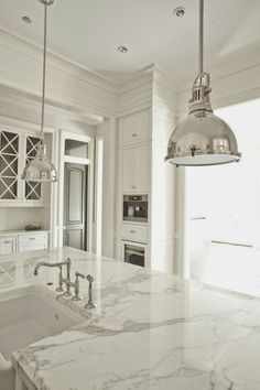 Love this white kitchen, beautiful countertops and light fixtures.  #interiors