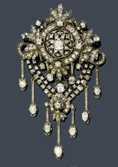 DIAMOND BROOCH, ca. 1880. Silver over pink gold. Fancy, floral open-worked brooch with circle, bow, palmette and leaf motifs, and 5 pendants with old European cut diamonds as the lower part. Below, a double garland with a palmette motif and 7 flexibly mounted, diamond-set pendants. With a total of 22 old European cut diamonds weighing ca. 3.50 ct and numerous old European cut diamonds and rose-cut diamonds weighing ca. 2.80 ct. Ca. 9.5 cm.
