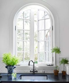 The inspiration: English cottages  The project: This gracefully arched casement window replaced a window half its size, says designer Jane Schwartz, who craved more light and a better view of her garden from the kitchen. To reinforce its old-world flavor, she kept the wall clear of upper cabinets and finished the sink with a porcelain-lever-handle bridge faucet.