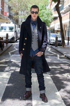 Men's Black Sunglasses, Navy Longsleeve Shirt, Grey Wool Waistcoat, Navy Overcoat, Navy Jeans, and Burgundy Leather Boots