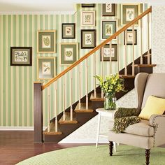 Rather than being excluded from the adjoining room, this staircase is seamlessly integrated into the space with color-complementary wallpaper and artwork. Narrow vertical stripes on the far wall add charm, and botanical artwork with matching green mattes add fresh detail. Painted an earthy chocolate brown, the stair forms and railing seem to ground the space's dominant earthy pastel palette.