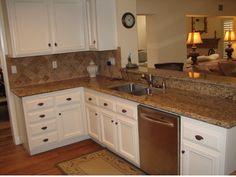 Remodelar cocina: Tope de granito marron, ceramica crema, gabinetes blancos.