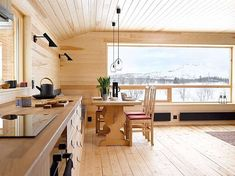 VIEW: The window is the cabin's eye in the mountains. Although the open space is open, it is warm and intimate. The seat bench at the dining table is an extension of the kitchen interior [a
