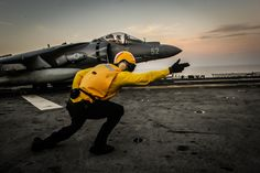 ARABIAN GULF(Oct.22,2013)Aviation Boatswain's Mate 2nd Class Austin Moore directs AV-8B Harrier II from 13th Marine Expeditionary Unit (13th MEU) before it takes off from flight deck aboard amphibious assault ship USS Boxer (LHD 4).Boxer flagship for Boxer Amphibious Ready Group &,with embarked 13th MEU,is deployed in support of maritime security operations & theater security cooperation efforts in the U.S. 5th Fleet area of responsibility.(USN Mass Comm Spec 3rd Class Brian Jeffries)