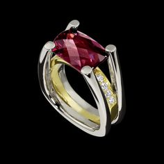 Fortessa Garnet Ring, a modern ring design by Adam Neeley, shows elegance and strength. This design features a stunning 6.85 carat Rhodolite garnet cut by lapidary Stephen Avery, accented by .25 cttw of F/G VS diamonds, set in two tones of gold.