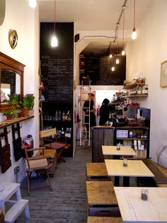 Eclectic and cosy with rustic charm, love the chalkboard menu. with the patterned tables along with the lighting very cute little cafe