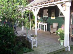 Tuinaanleg landelijke overkapping terras met houten vlonders.