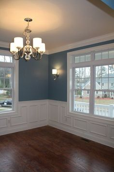 Beautiful color palette--Benjamin Moore's Labrador Blue on the walls, lots of white millwork, and glossy brown stained floors. Blogger says that Labrador Blue is a very strong color and needs to be offset with white to keep it from overpowering everything else.
