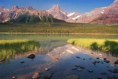 Placid lake reflecting rocky mountains.