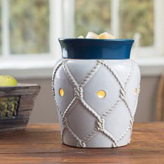 "Nautical Illumination Availability: Allow 3-4 Business Days to Ship This nautical inspired warmer has an eggshell reactive glaze with an embossed fishing net and topped with a navy blue dish. Uses a soft halogen bulb to create a warm glow and release the scent of your favorite fragrance. Dish is removable and includes the warming bulb.Warmer Details:⦁	Length: 4.5""⦁	Width: 4.5""⦁	Height: 6.5""⦁	Electrical Rating: 120V, 60Hz, 25W⦁Bulb Type:NP5 25 Watts⦁	Switch Type: Dial Switch Ships from PA by…"