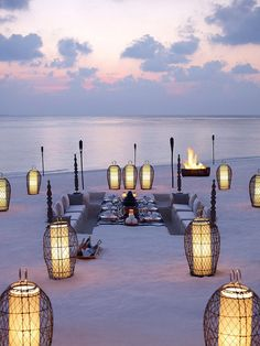 beach dugout seating and lanterns at sundown - amazing Dusit Thani Maldives