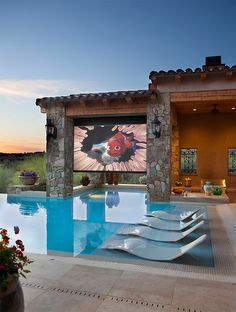Outdoor pool with seats and movie screen.