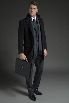 Camisa branca sobreposta por gravata de seda preta com padrão micropaisley, tricô cinza em gola V e costume chumbo. O cachecol de tricô e o casaco de lã preto caracterizam a produção de inverno, indicada para um ambiente formal e sofisticado.
