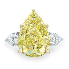 Fancy Yellow Diamond and Diamond Ring /Platinum, gold, centering one pear-shaped Fancy Yellow diamond* approximately 13.33 cts., flanked by 2 pear-shaped diamonds approximately 1.60 cts., approximately 6.4 dwt.