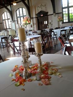 McBryde Hall wedding centerpiece--silver candlesticks with pillar candles. Pink/peach flower petals. Mixed centerpieces. Some tall, some small.