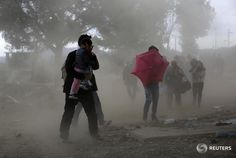 Eefugees protect themselves from gusts of wind and dust at Greece's border with FYRO Macedonia. Yannis Behrakis