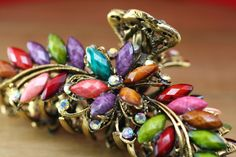 This vibrant, colorful jaw clip makes for an eye-catching hair accessory. It features multi-colored stones with a centered floral design and