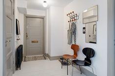 szare drzwi w przedpokoju z białą podłogą,czarnym i brązowym krzesłem,prostokatnymi lustrami bez ram i metalowym wieszakiem z drewnianymi gałkami