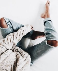 Gray cable knit sweater with trendy distressed denim jeans.