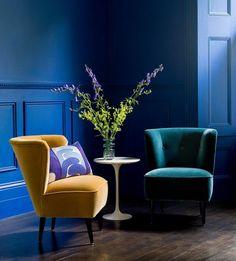 deco bleu canard et bleu marine, parquet marron foncé, fauteuil jaune, table d appoint blanche, fleurs, decor dramatique