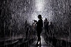 People visit the Rain Room, an installation by artists Random International, at a museum in Shanghai, China