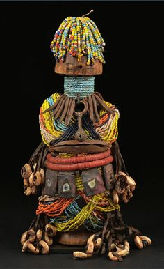 Africa | Fali doll from northern Cameroon | Wood, glass beads, leather strips, cowrie shells, coloured discs, leather amulets with mirror, iron amulets