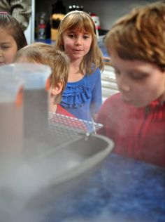 For a Science Party for 7 year olds we filled plastic science beakers with drinks which we stood on a cooling rack over a roasting pan and then we put dry ice in the pan to create smoke.  The kids loved it.
