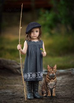 Pretty little girl in beret and boots holding staff with tabby cat seated beside her